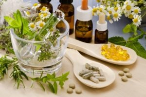 19914033 - alternative medicine. rosemary, mint, chamomile, thyme in a glass mortar. essential oils and herbal supplements.
